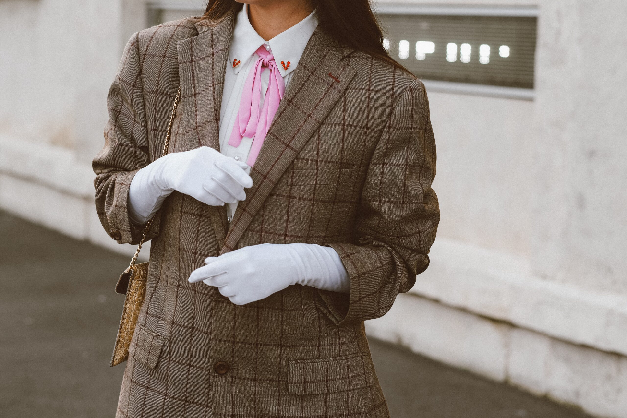A woman in a checked suit with a white shirt and gloves