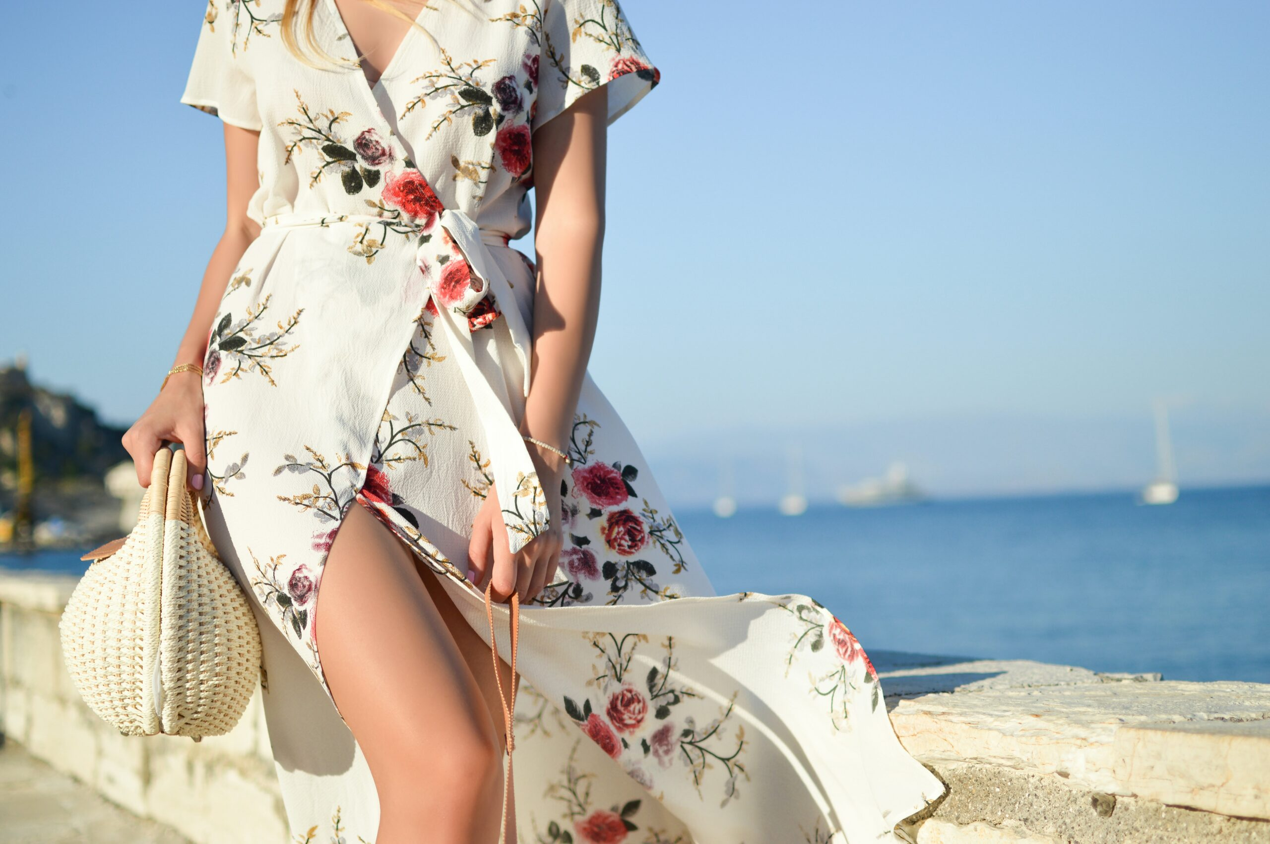 A lady walking by the sea in a white floral maxi dress