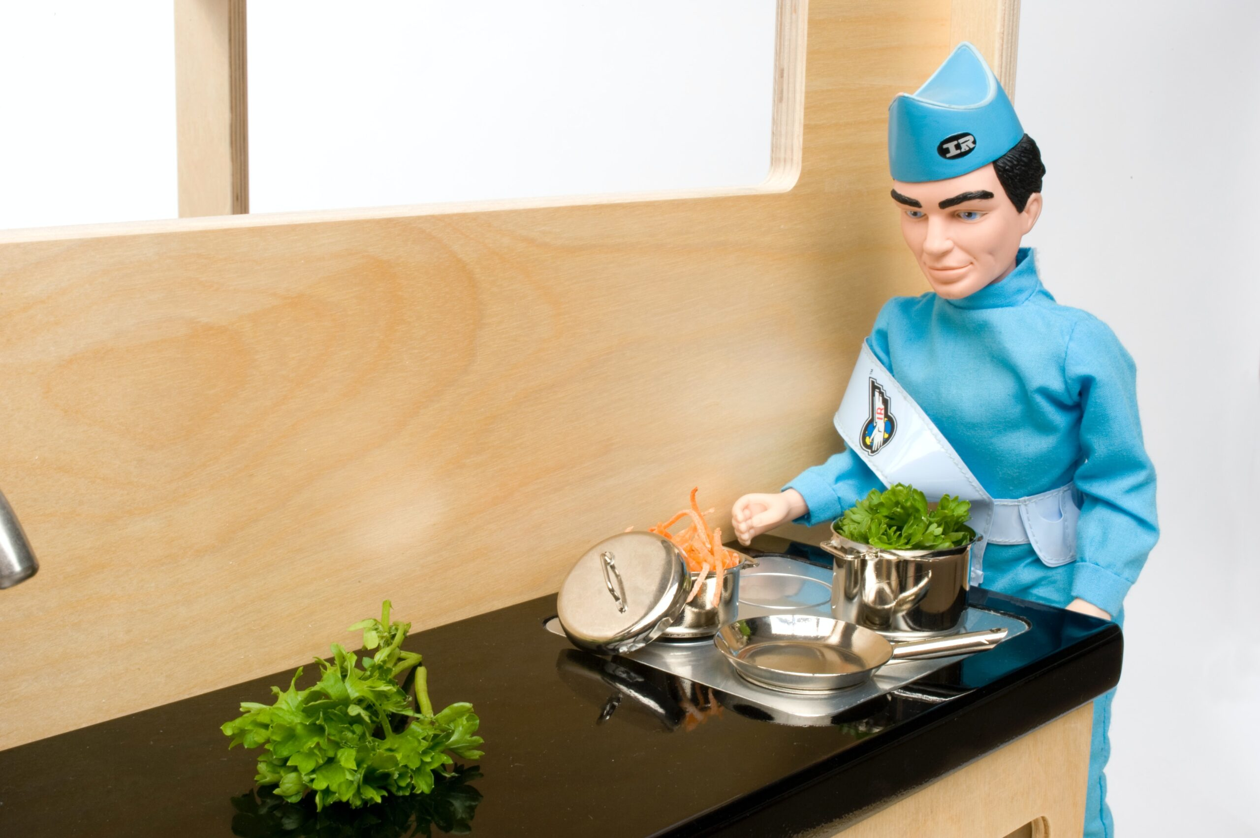 A Thunderbirds character standing in a toy kitchen