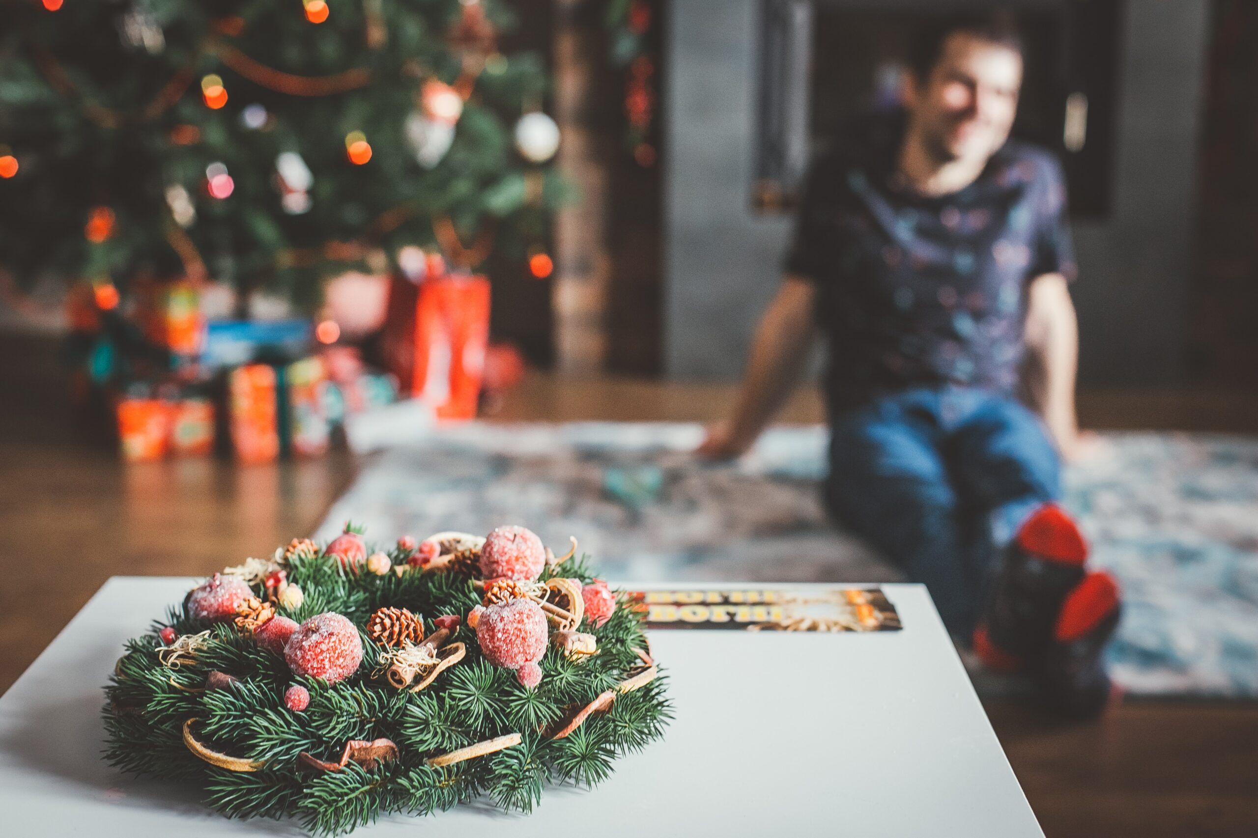 A man sitting on a rug watching a Christmas film, with a Christmas tree and a wreath