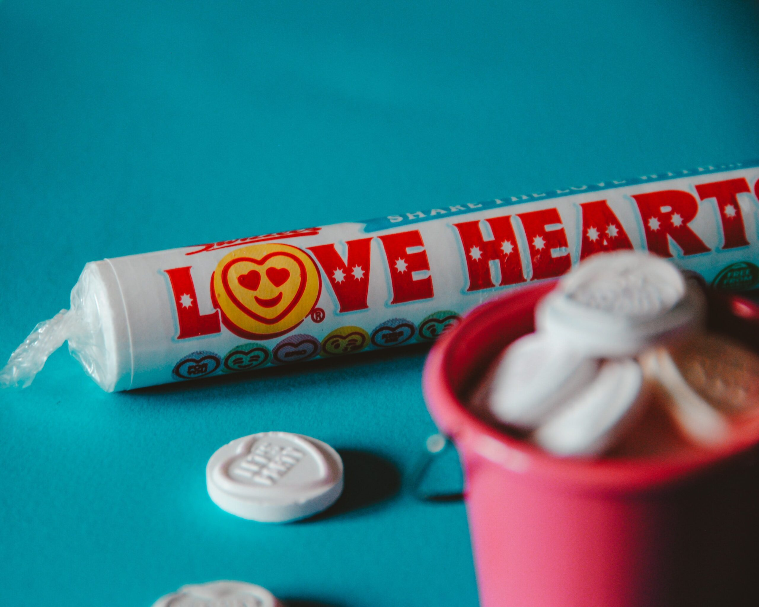 A packet of Love Hearts sweets on a blue table