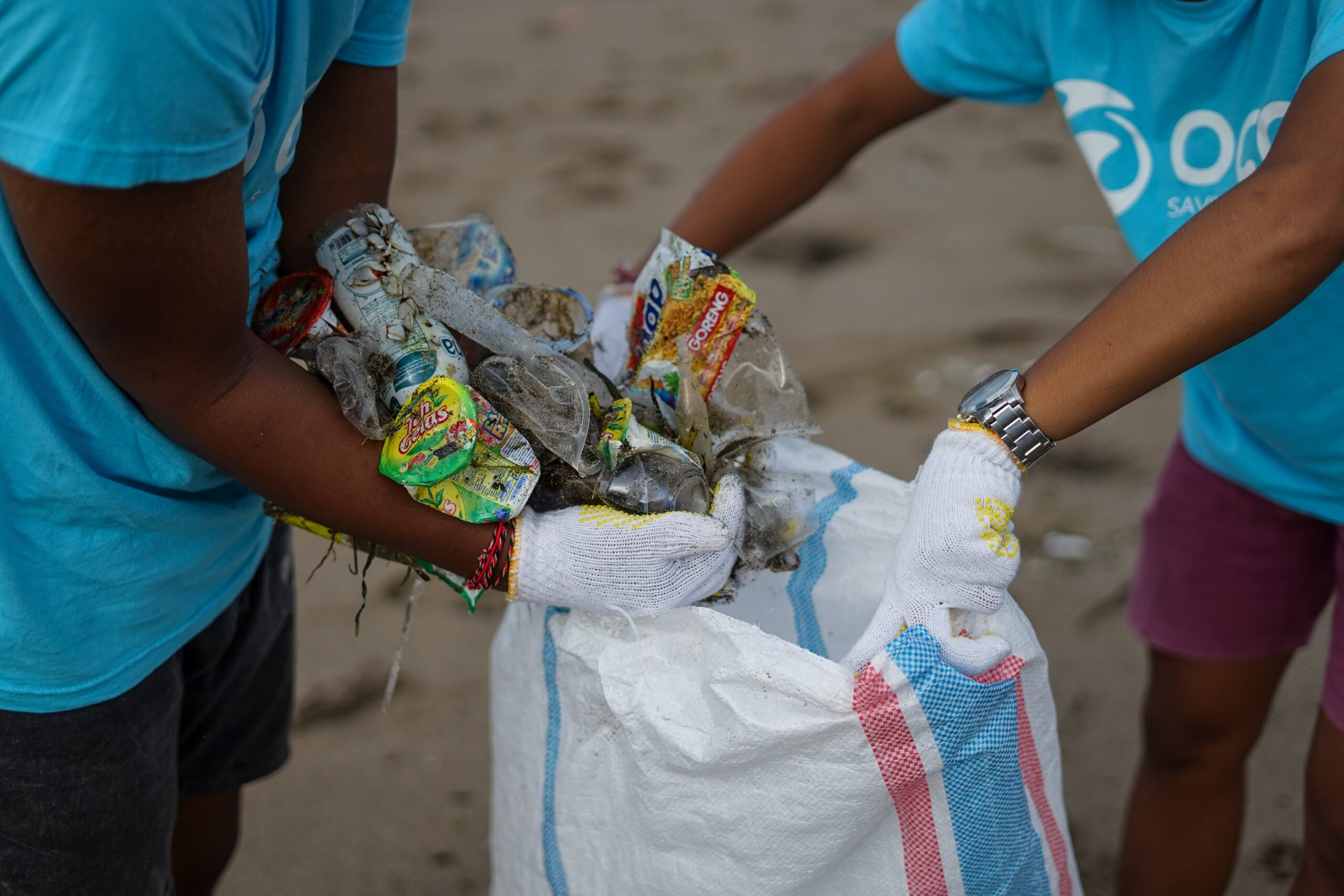 Two people clearing up plastic waste from a beach